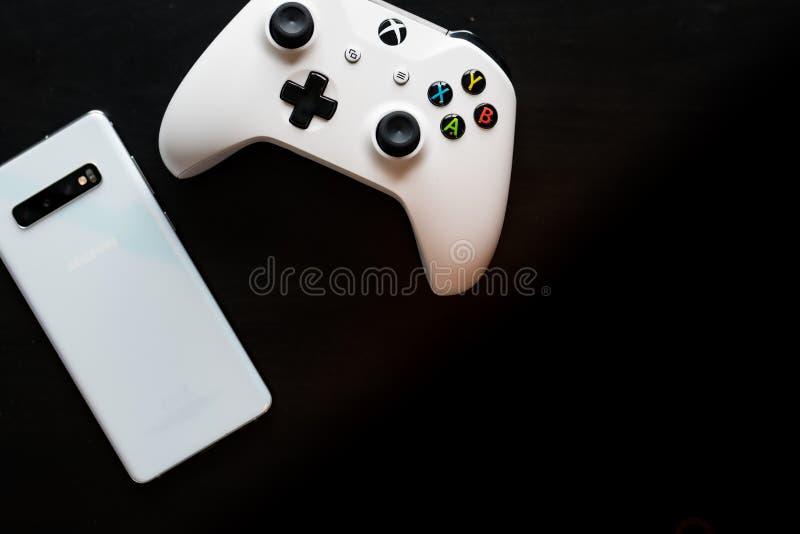 En telefon och en kontrollant sitter sidan - vid - sidan som att spela blir m?ng--plattformen royaltyfri foto