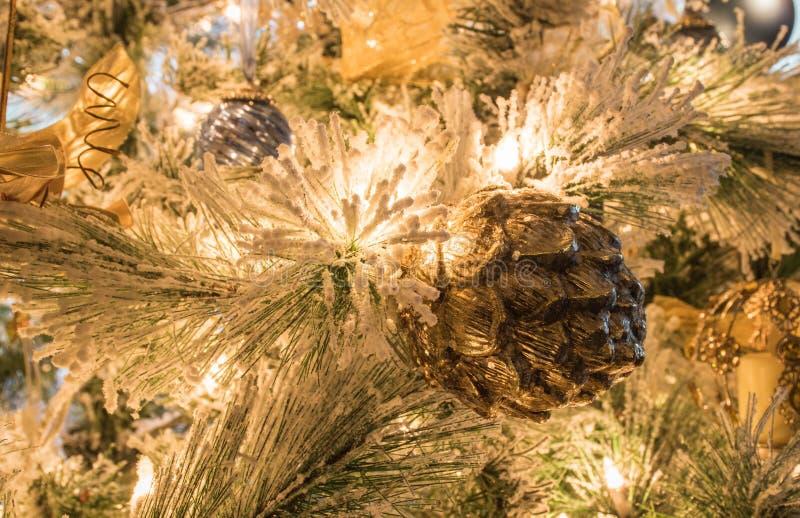 En texturerad guld- pineconejulprydnad på en flockas julgran arkivfoto
