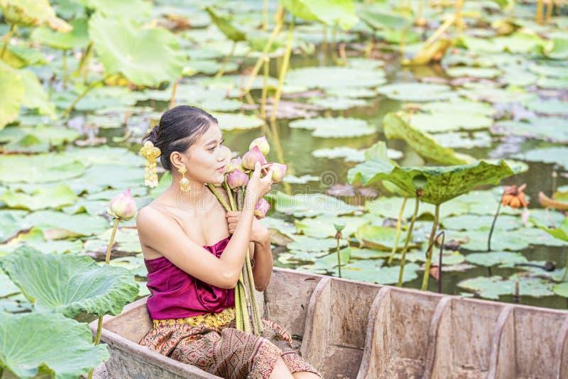 En thailändsk kvinna sitter på ett träfartyg och samlar rosa lotusblommablommor Kvinnlig rodd på sjöskördnäckrors _ royaltyfria foton