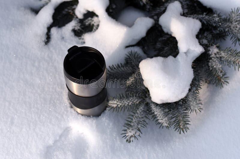 En thermocup av kaffe mot den snöig skogbakgrunden för vinter royaltyfri fotografi