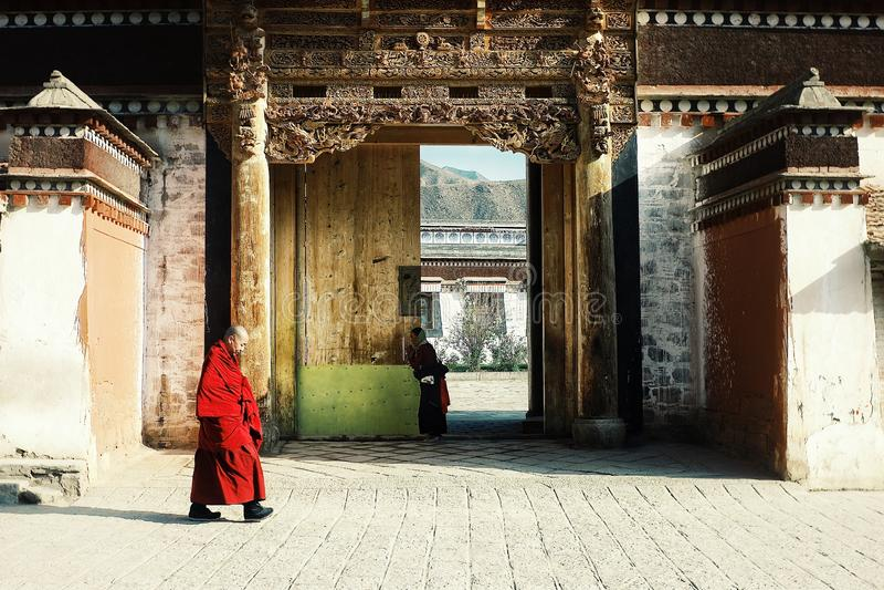 en tibetan munk som förbi går vid en av templet medan en vallfärdakvinna som ber i bakgrunden arkivbilder