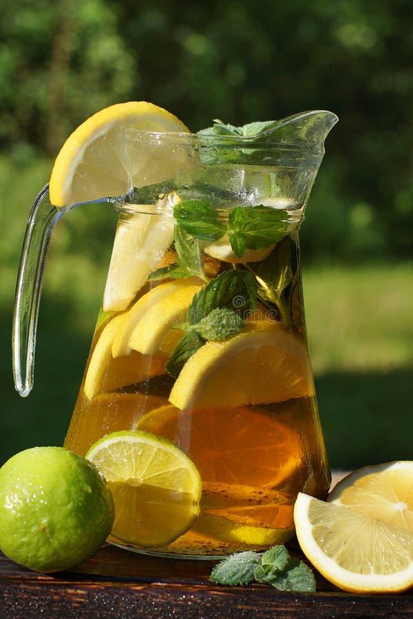 En tillbringare av kallt te med citronen och mintkaramellen, en smutt av friskhet på en varm sommardag arkivbild