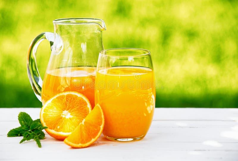 En tillbringare och ett exponeringsglas av ny orange fruktsaft fotografering för bildbyråer