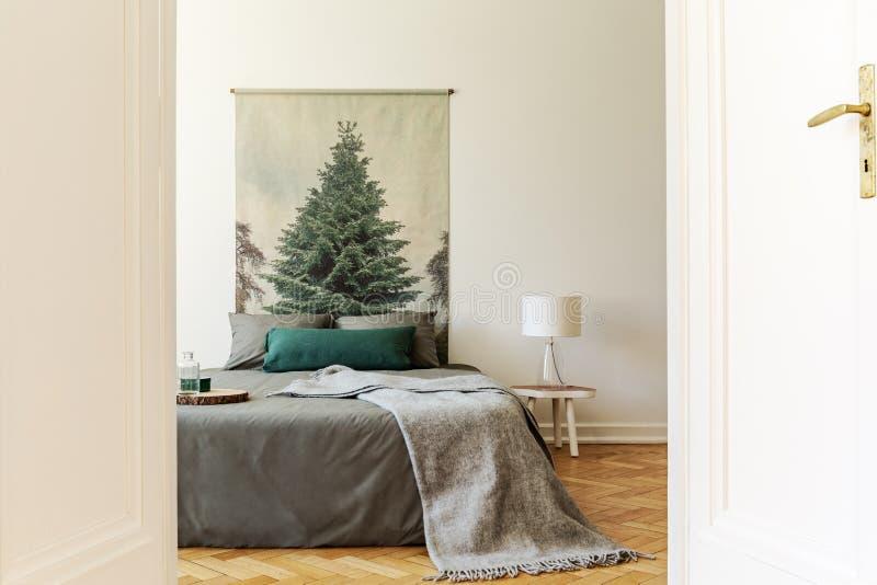 En titt till och med en öppen dörr in i en enkel stilsovruminre med grå färg- och gräsplanark för säng en iklädd, kuddar och ull  royaltyfri foto