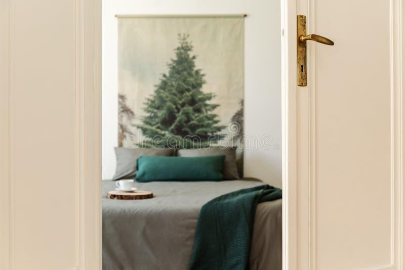 En titt till och med en öppen dörr in i en sovruminre som är suddig En säng med gräsplan och grå färglinne och kuddar mot wi för  royaltyfria bilder