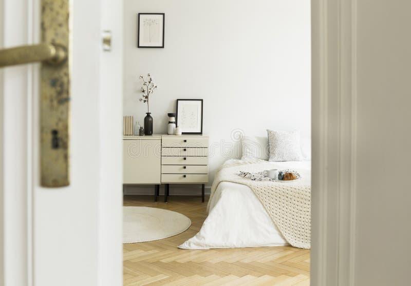 En titt till och med en halvöppen dörr in i en monochromatic beiga- och vitsovruminre med en säng och ett enhetskabinett Verkligt arkivfoton