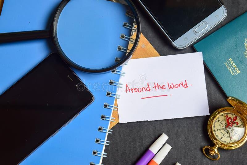 En todo el mundo escrito en el papel pasaporte, lupa, compás, Smartphone imagen de archivo libre de regalías