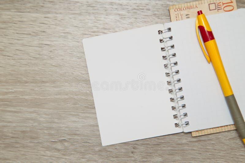 En tom anteckningsboksida och penna med colombianska pesos på den wood kontorstabellen royaltyfri bild