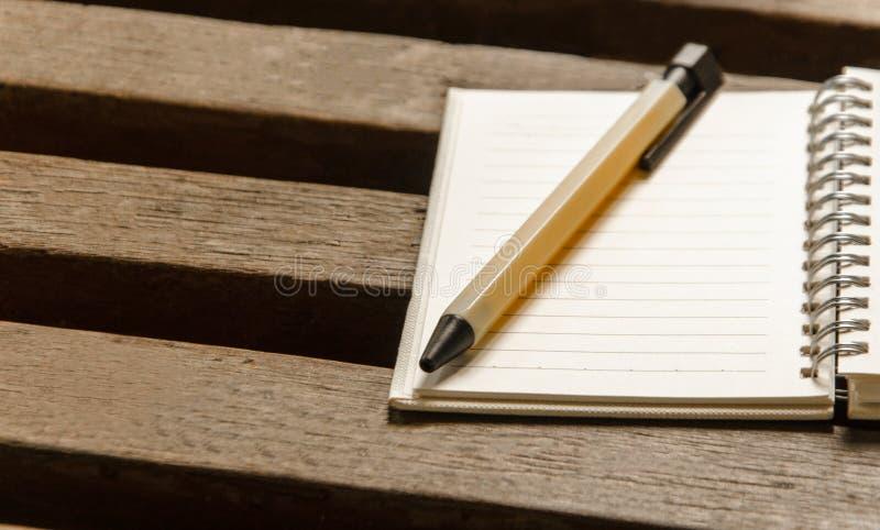 En tom anteckningsboksida och penna på den wood tabellen Bästa sikt med kopian royaltyfria bilder