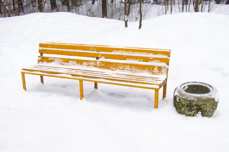 En tom bänk i en vinter parkerar En tom träbänk i parkerar, lite varstans i snön Snö-täckt gränd med tomma bänkar royaltyfria bilder
