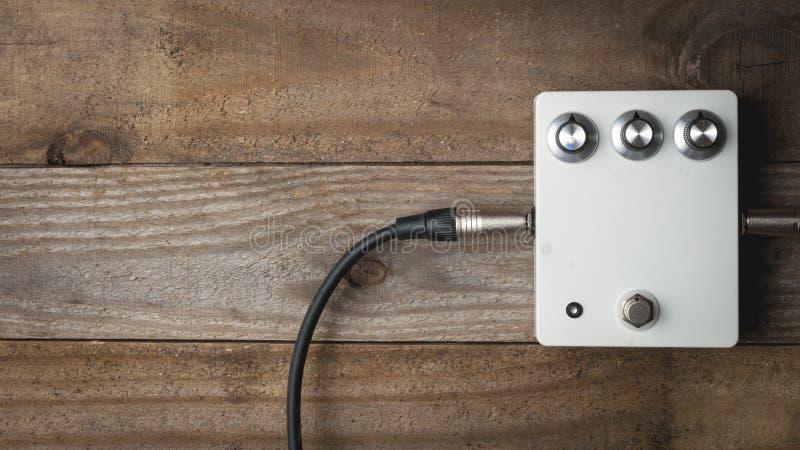 En tom vit gitarrpedal med tappningknoppar och pluggade stålar på trägolv royaltyfria bilder