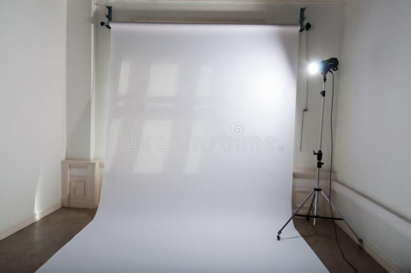 En tom yrkesmässig fotostudio med ren och enkel aktivering för fotografisk utrustning av den vita vanliga pappers- bakgrunden och fotografering för bildbyråer