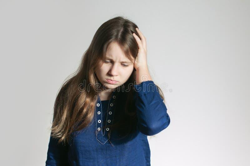 En tonårig flicka i en blå klänning med en huvudvärk som rymmer hennes huvud med en arm som inte ser en kamera royaltyfria foton