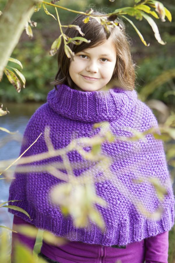 En tonårig flicka med lila poncho arkivbild