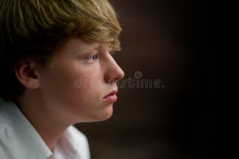 En tonårig pojke för blont hår med blåa ögon ser tankfull. royaltyfria bilder