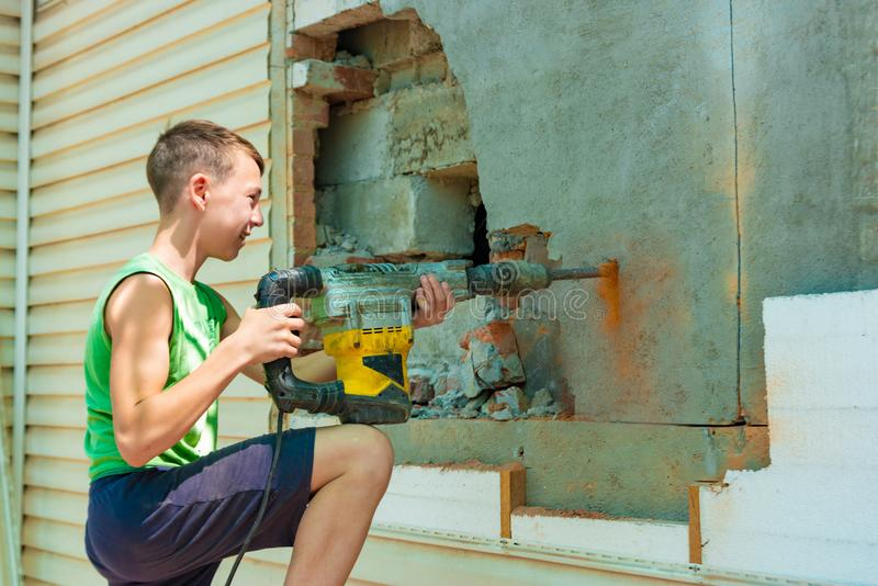 En tonåring arbetar på en konstruktionsplats genom att använda en elektrisk tryckluftsborr, begreppet av att exploatera barnarbet fotografering för bildbyråer