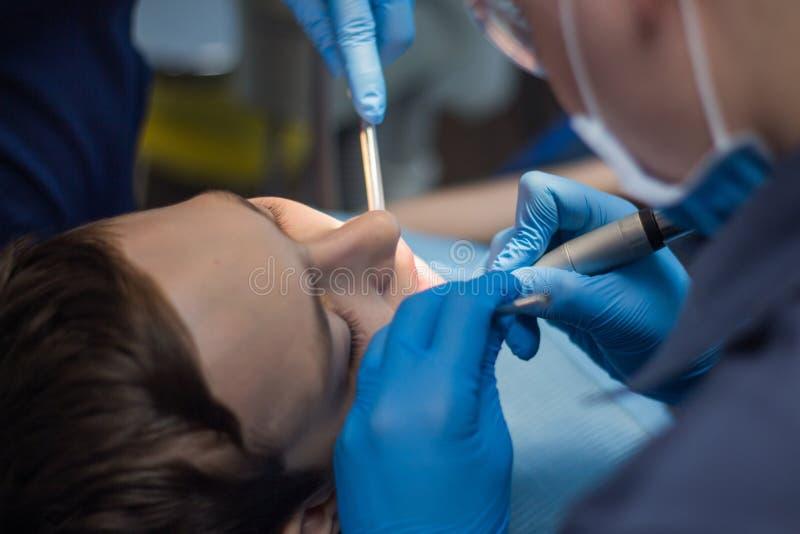 En tonåring behandlar tänder i tandläkekonst Doktorn av tandläkaren och assistenten för den tålmodiga erkännandet för ` s Närbild royaltyfria foton