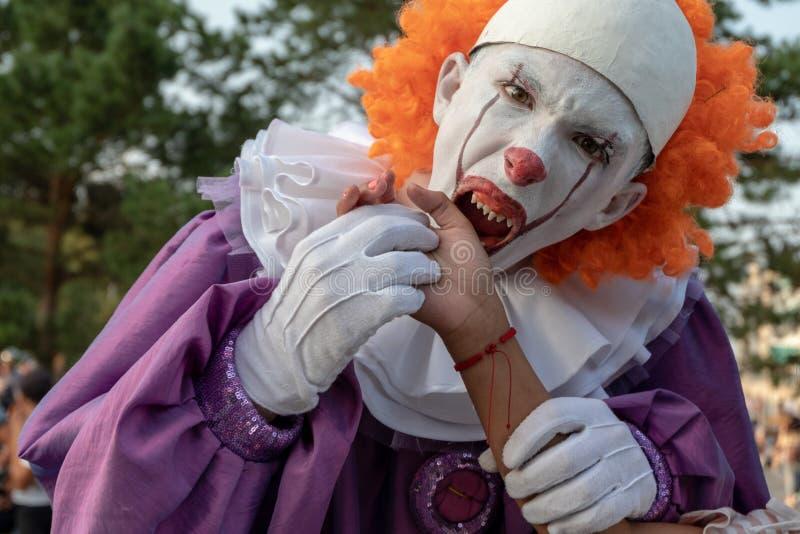 En tonåring i en ond clown med vassa tänder låtsas bita någons hand En kille på gatan, Halloween cosplay fotografering för bildbyråer