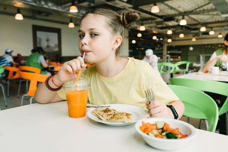 En tonåringflicka sitter i ett kafé som dricker en morotsmoothie och äter pannkakor royaltyfri foto