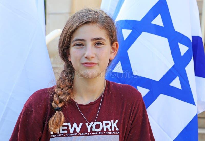 En tonårs- flicka bredvid en israelisk flagga royaltyfri bild
