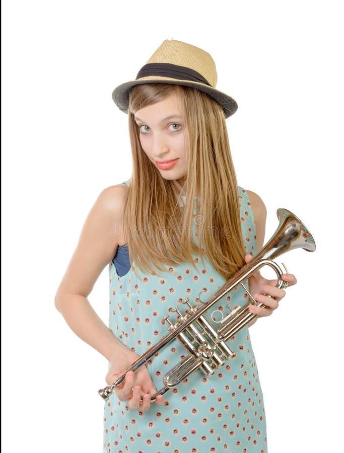 En tonårs- flicka med en trumpet och en hatt royaltyfria bilder