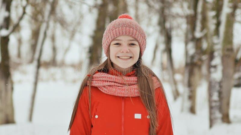 En tonårs- flicka med fräknar på hennes framsida ler lyckligt in i kameran En bakgrund av ett vinterskoglandskap fotografering för bildbyråer