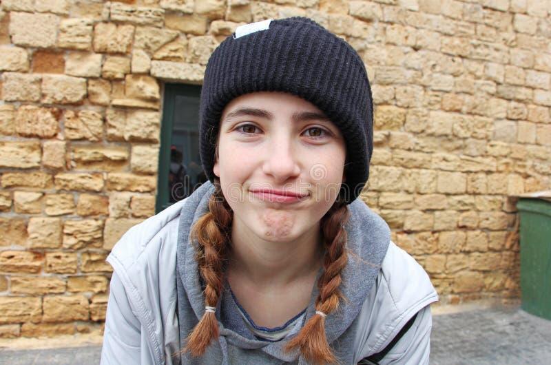 En tonårs- flicka med en stucken hatt royaltyfria bilder