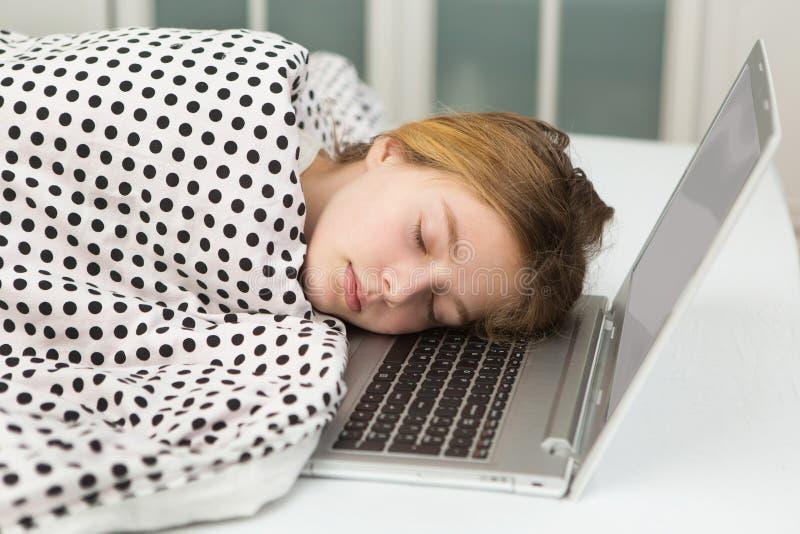 En tonårs- flicka sovande på en dator royaltyfri bild
