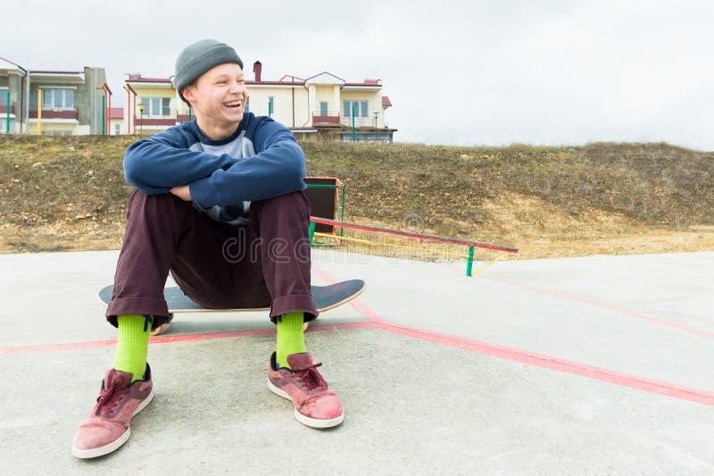 En tonårs- pojke sitter på en skateboard i parkera och le Begreppet av tidsfördriv för fri tid för tonåringar i royaltyfri fotografi