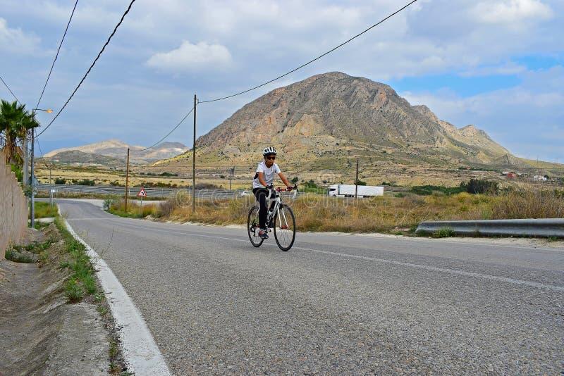 En tonårs- pojke som cyklar, i att bedöva landskap royaltyfria foton