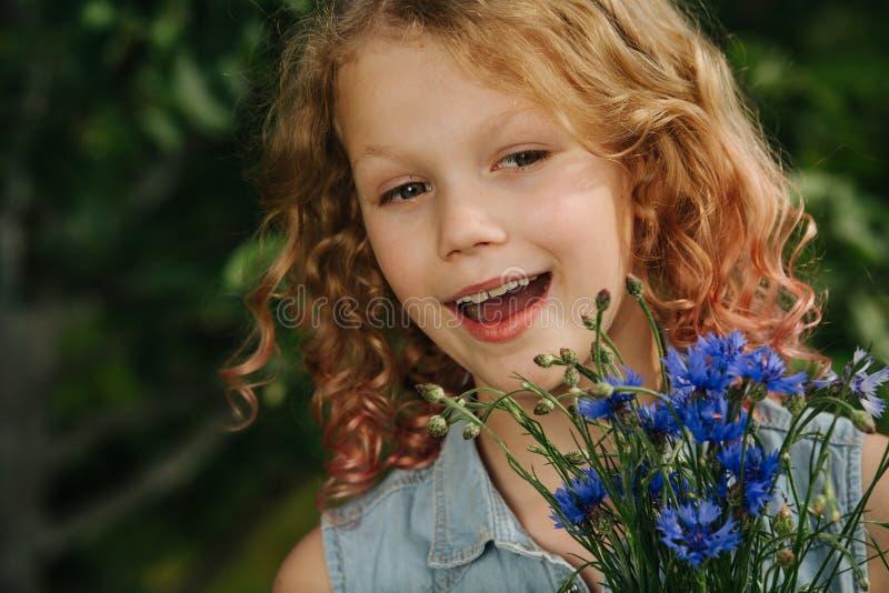 En tonårsflicka med hårstrå håller en blå bukett av ängsblommor royaltyfri bild