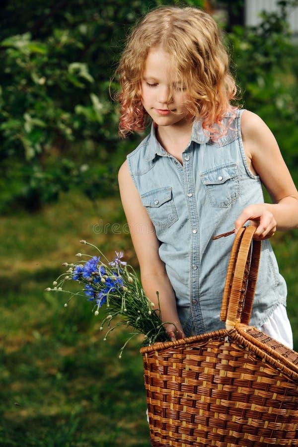 En tonårsflicka med hårstrå håller en blå bukett av ängsblommor arkivbilder