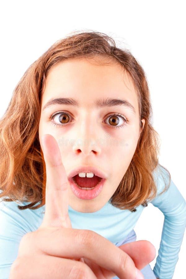 En tonflicka berättar något genom att höja sitt pekfinger Emotionell flicka isolerad royaltyfri bild