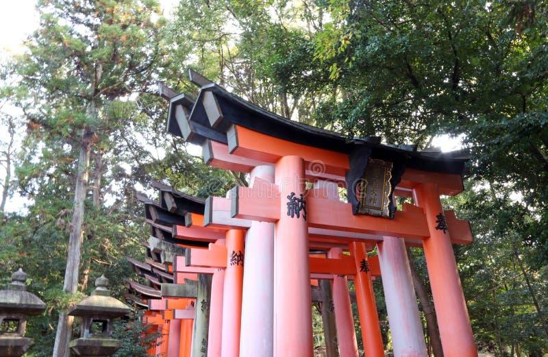 En torii på den Fushimi Inari relikskrin, köpmän och producenter har traditionellt tillbett den Inari guden arkivbild