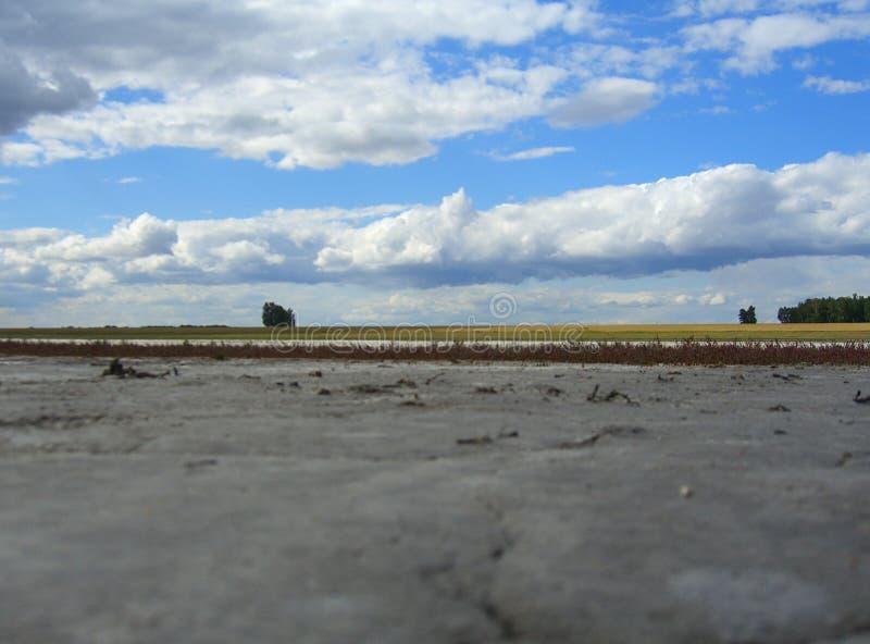 En torkad-upp flodbädd av saltar sjööknen den nakna botten av behållaren i Kasakhstan med landskap för natur för stormmoln royaltyfri fotografi