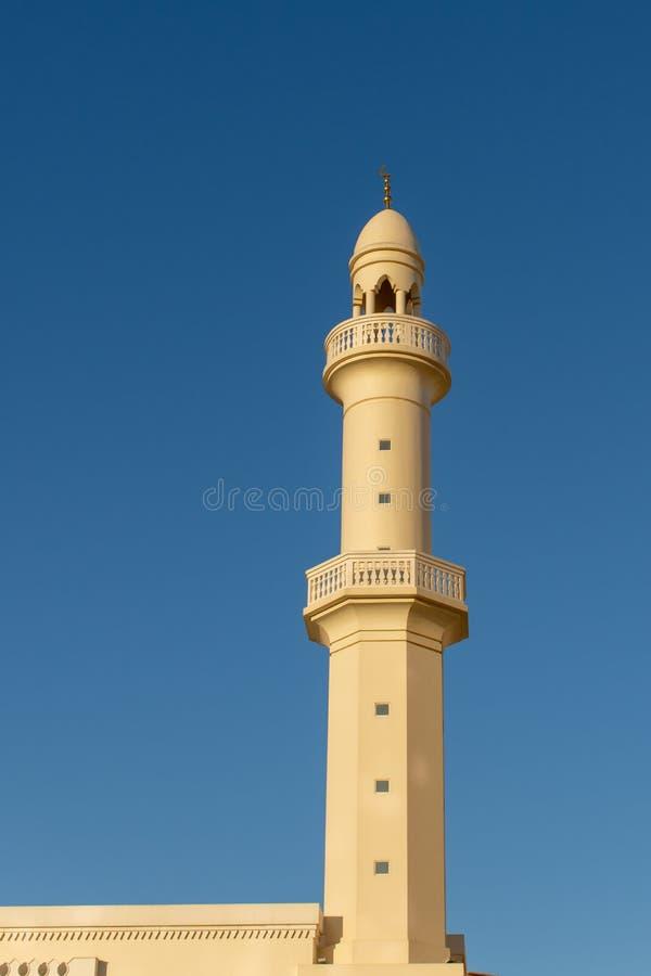 En tornspira och en minaret av en vit och orange moské med en bakgrund för blå himmel royaltyfria foton