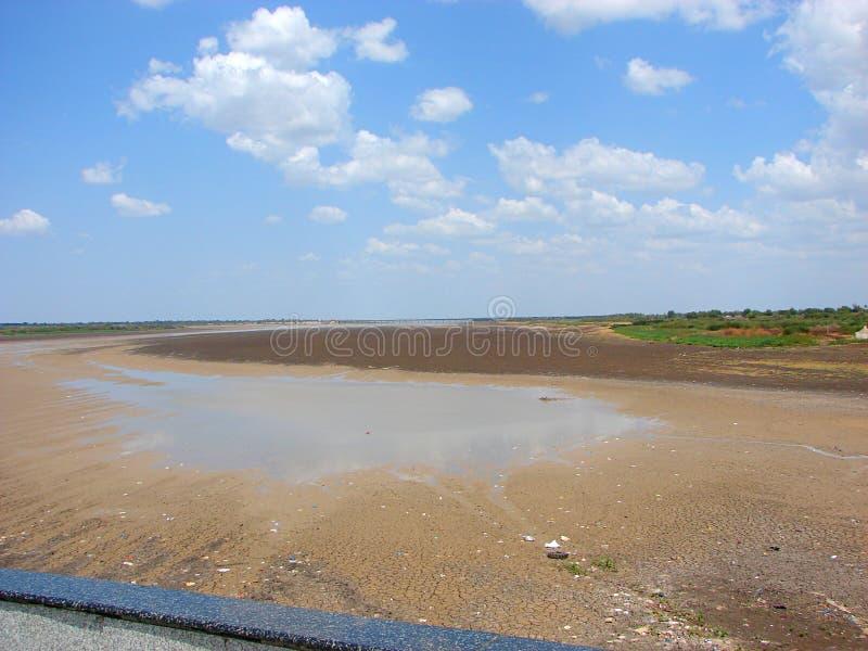 En torr flodbädd på tid av svält i varm sommar arkivbild