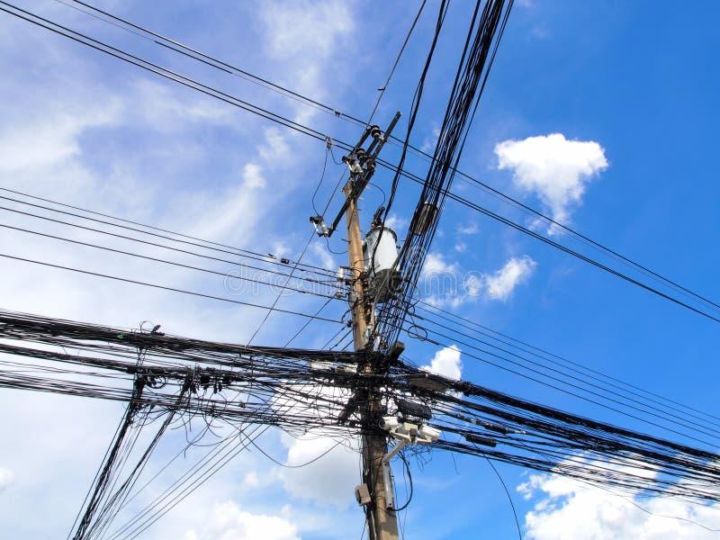 En tova av kablar och trådar på hög-spänning maktpol arkivbild