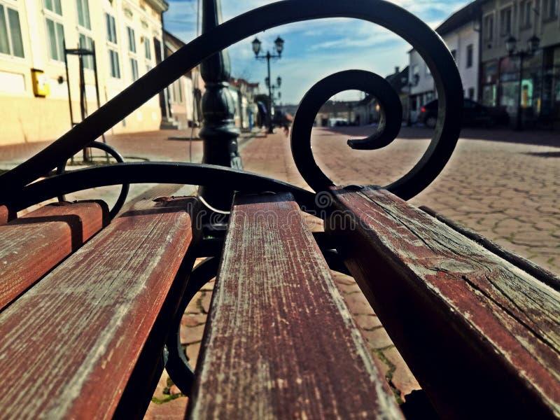 en träbänk i mitten av en gullig liten stad i Serbien arkivbild