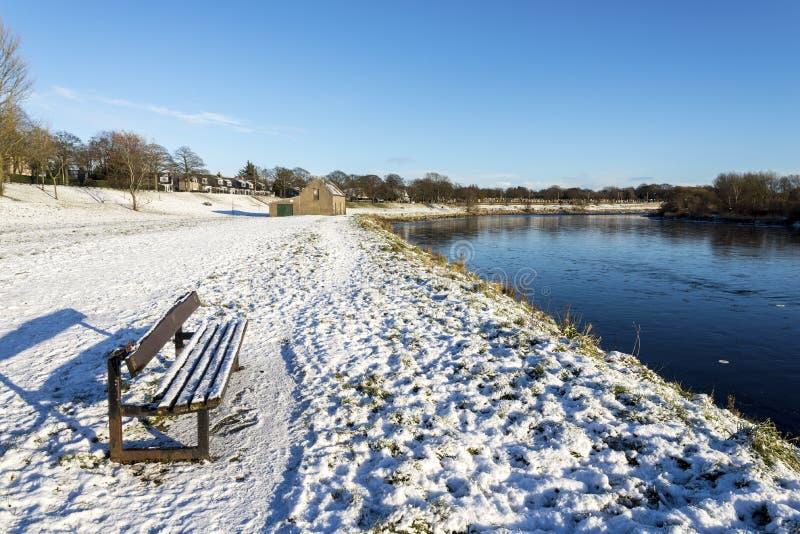 En träbänk täckt av snö nära floden Dee, Aberdeen, Skottland arkivbild
