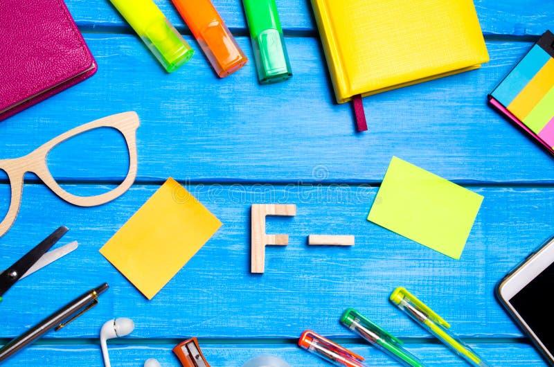 En träbokstav av kvalitet F negativ skrivbordet för student` s Skolatillförsel på en blå trätabell Begreppet av högre skola arkivfoto