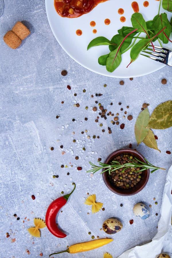 En träbunke för att krydda bredvid en maträtt på en grå bakgrund Kryddor med varmt färgrikt peppar, lagerbladar och a arkivbild
