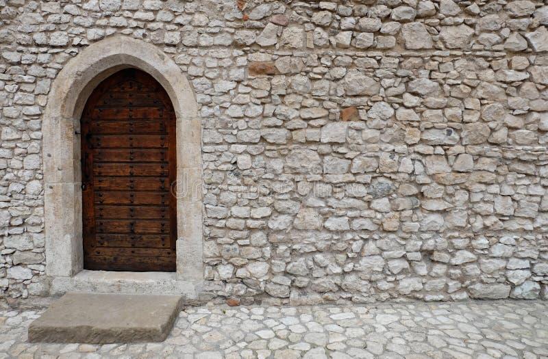 En trädörr med den spetsiga gotiska stilbågen i en stenvägg arkivbilder
