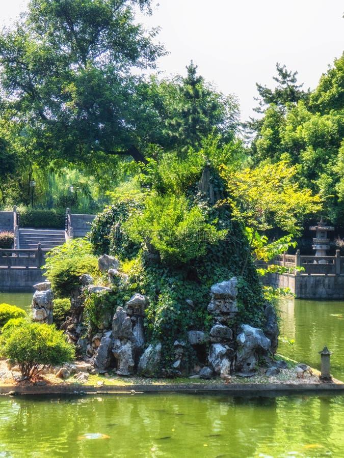 En trädgård med fiskpölen, stenar bron och paviljonger, Hangzhou, Kina arkivbilder