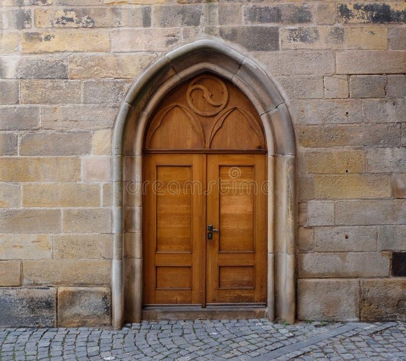 En trädubbel dörr med den spetsiga gotiska bågen i en vägg som göras av stenkvarter royaltyfria foton