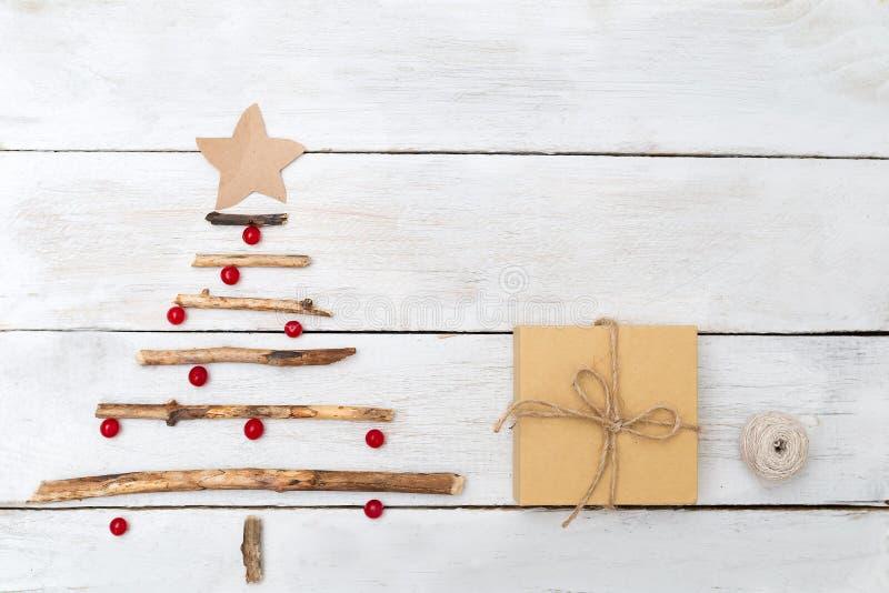 En träjulgran med bär av en viburnum och en gåva bo royaltyfri foto