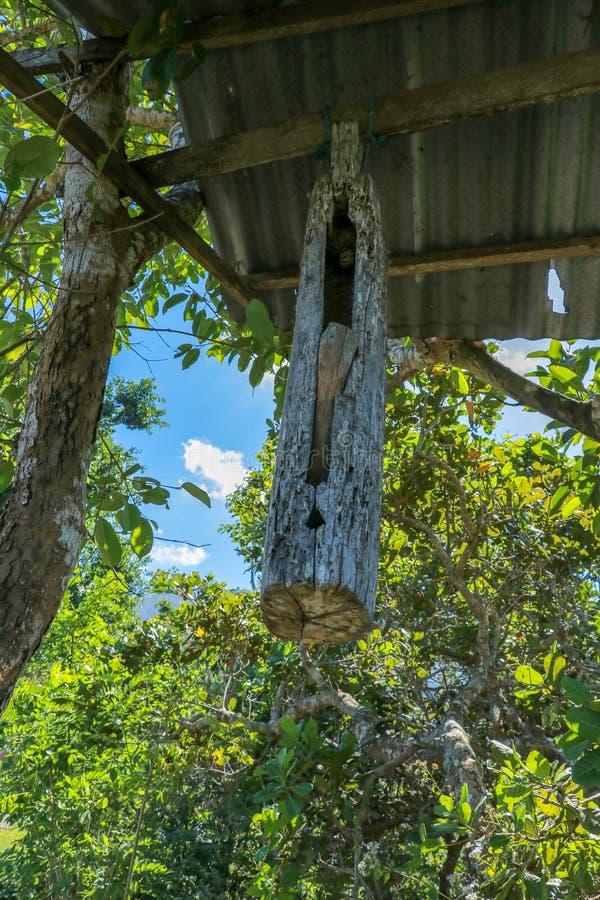En träklocka med en klubba som gjordes från en trädstam, hängde på en stråle mellan träd på den Bali ön Balinesen Hindus gör kloc royaltyfri bild