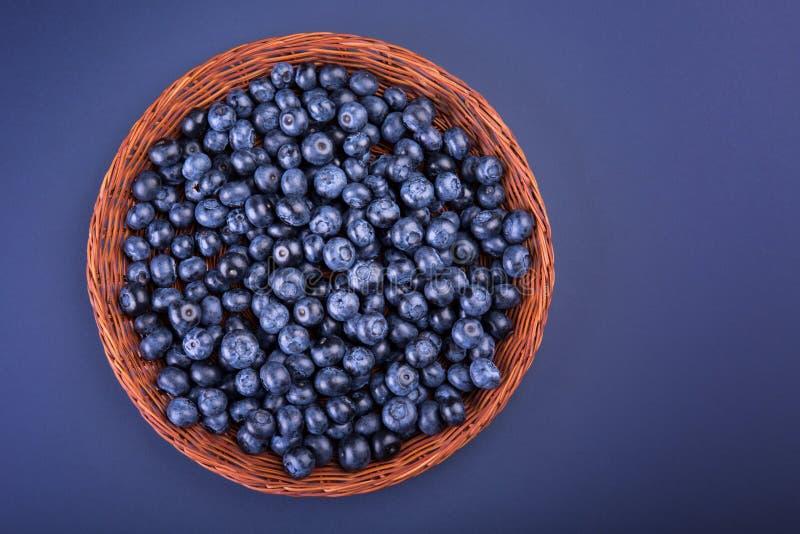 En träkorg med saftiga och bittra blåbär på en mörk purpurfärgad bakgrund, bästa sikt En spjällåda mycket av bär royaltyfri fotografi