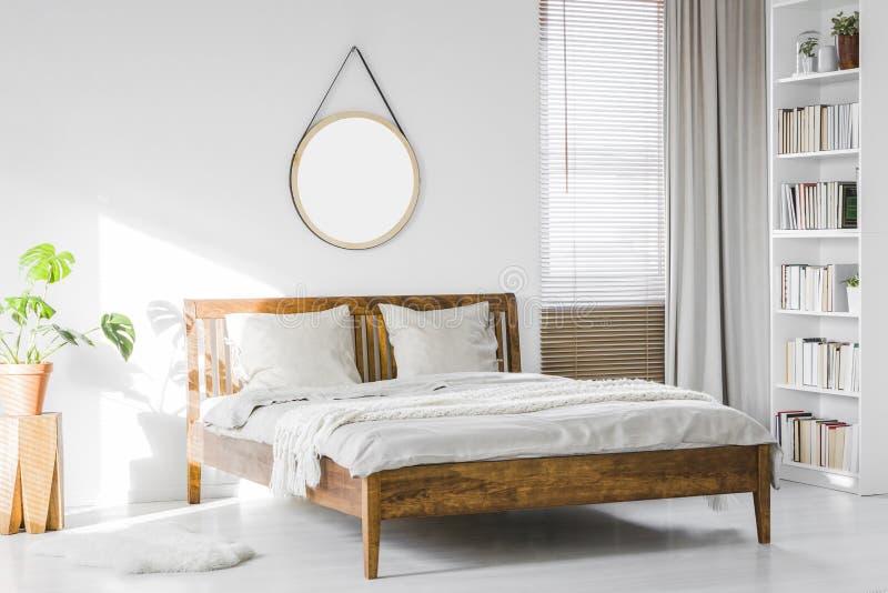 En trälantlig sängram och en bokhylla för hem- arkiv i en natur royaltyfria bilder