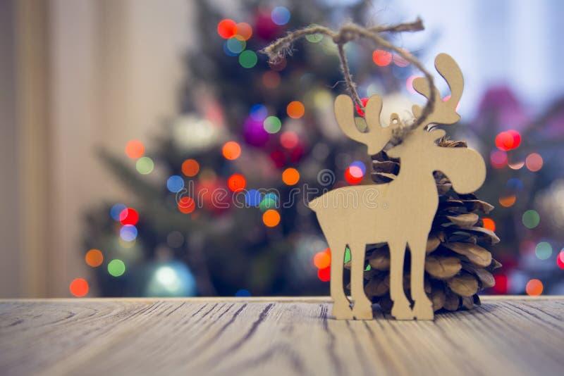 En träleksakälg på en trätabell mot den dekorerade julgranen royaltyfri foto